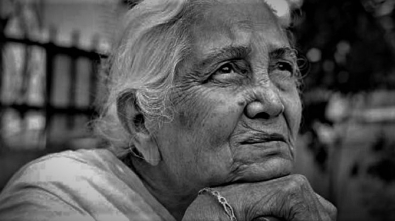 One sad pensive senior Indian woman looking up